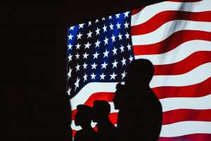 Silhouettes of people standing in front of the American flag.