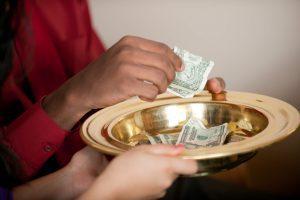 Parishioner placing cash in collection bowl
